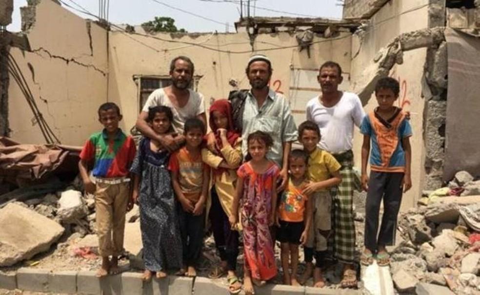A família Awal nos escombros de sua casa, atingida por dois ataques aéreos de forças sauditas - muitos ainda vivem nas ruínas de casas destruídas (Foto: BBC)