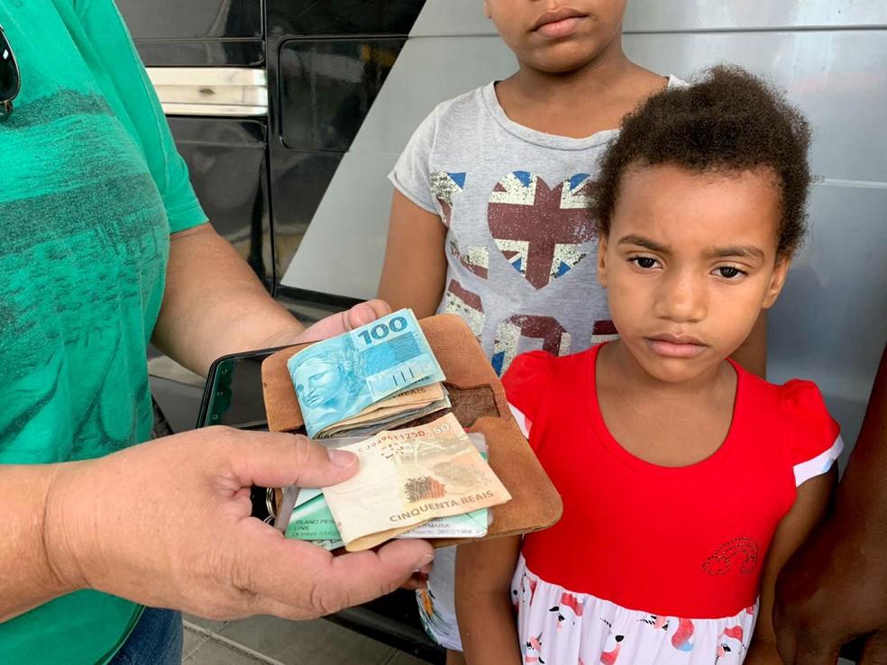 Ao lado de alguns dos filhos da mulher que achou sua carteira, Liliane Nakamura recebe tudo o que havia perdido na rua — Foto: J. Serafim/Divulgação