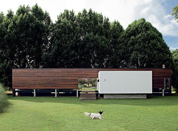 A frente desta casa de 567 m², feita pelo arquiteto Marco Peres, é fechada por réguas de itaúba, que a protege da insolação e forma atrás um colchão de ar com placa cimentícia. Em destaque, o volume branco abriga a cozinha (Foto: Edu Castello / Casa e Jardim  )