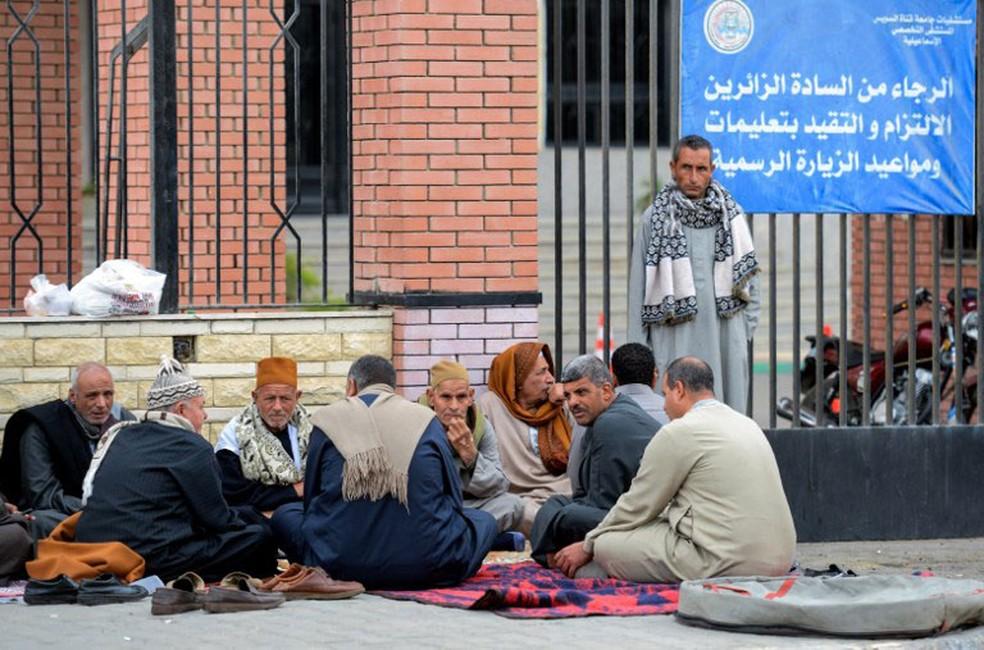 Parentes das vítimas de ataque contra a mesquita de Al Rawada aguardam informações fora do hospital da Universidade do Canal de Suez neste sábado (25) (Foto:  Mohamed El-Shahed / AFP)