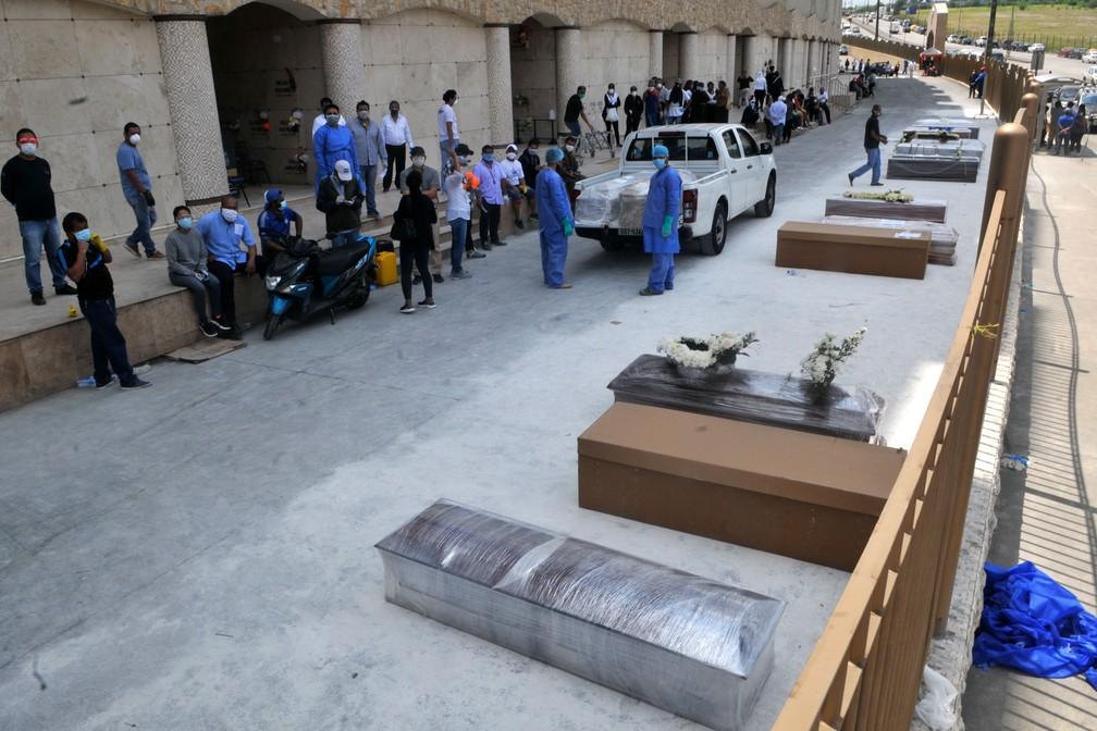 Pessoas esperam do lado de fora de cemitério de Guayaquil, no Equador, para enterrar familiares em caixões e caixas de papelão. Imagem do dia 6 de abril  — Foto: Jose Sanchez / AFP