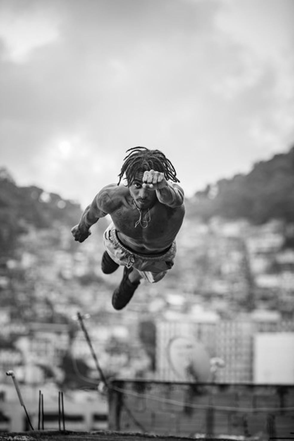 Foto mostra homem como se estivesse voando em uma comunidade — Foto: Reprodução / Favelagrafia