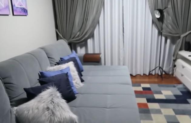 A sala de TV tem sofá grande e tapete colorido (Foto: Reprodução)