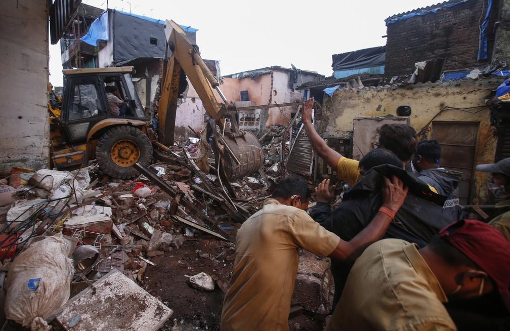 Equipes de resgate limpam os escombros em busca de desaparecidos após prédio de 3 andares desabar em meio às fortes chuvas de monções em Mumbai, na Índia, em 10 de junho de 2021 — Foto: Rafiq Maqbool/AP