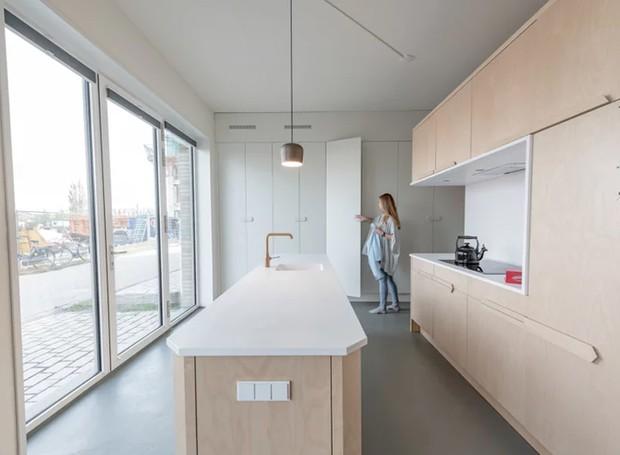 A luz da grande janela, instalada na parte de trás da casa, banha as áreas comuns (Foto: Tim Stet & Leonard Faustle/ Designboom/ Reprodução)