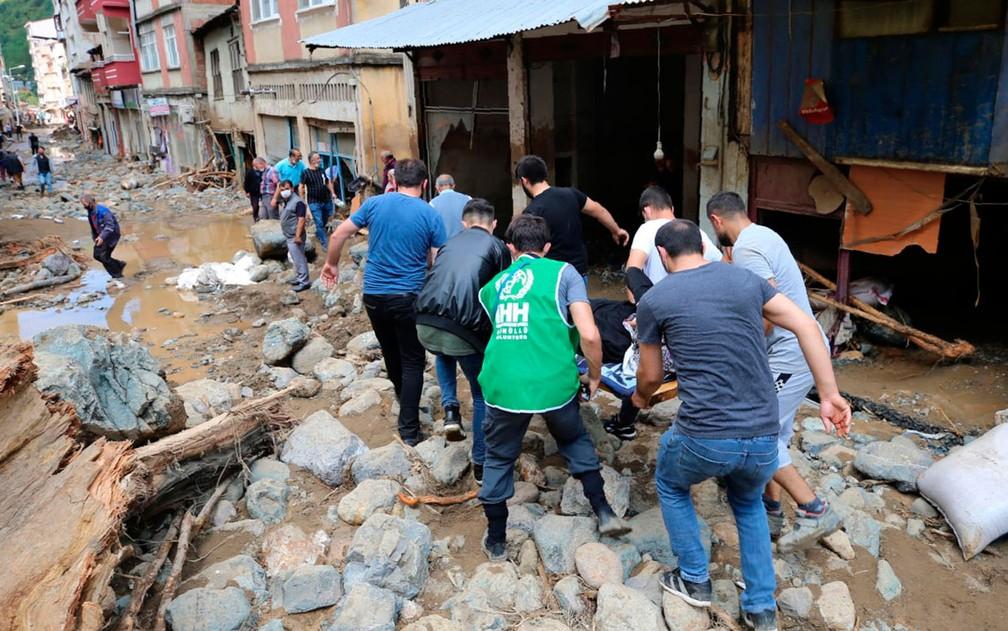 Pessoa ferida é retirada de escombros após inundação na cidade de Dereli, na província de Giresun, na Turquia, no domingo (23) — Foto: AP Photo
