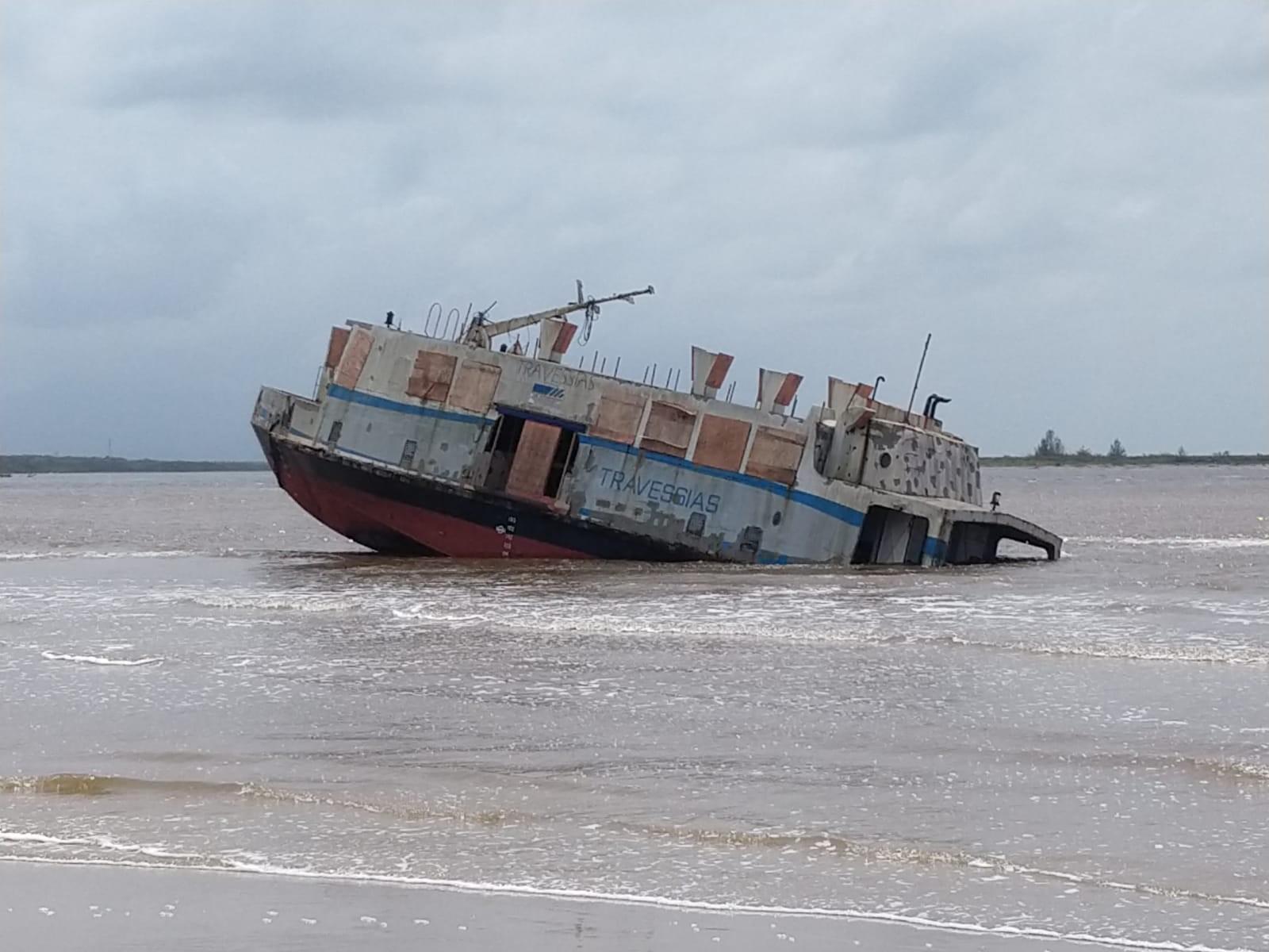 Embarcação encalhada em praia fica parcialmente submersa em Ilha Comprida, SP