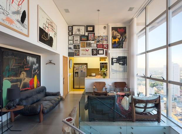 O sofá e duas poltronas Mole, com mais um par de poltronas Diz, todas criações de Sergio Rodrigues, preenchem a área social do apartamento. Ao fundo, a caixa amarela revela a cozinha (Foto: Paulo Rezende)