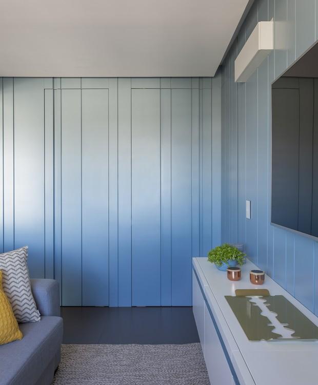 Só um olhar atento percebe as duas portas - do banheiro social e do quarto de hóspedes - escondidas entre as ripas do painel de laca azul (Foto: Marco Antonio/Divulgação)