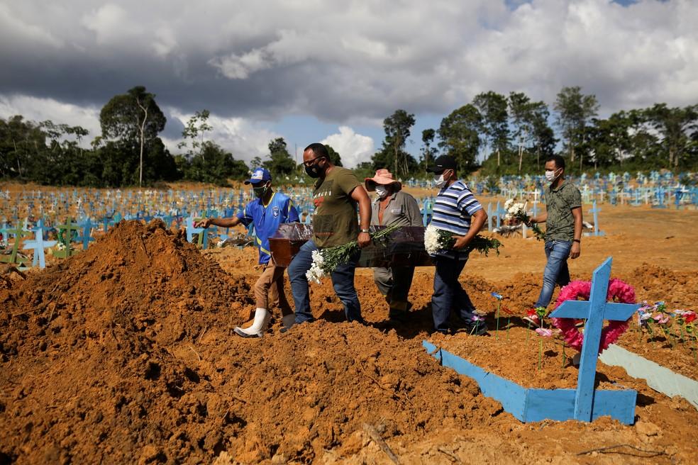 Filhos de Verônica Ferreira, de 73 anos, que morreu de Covid-19, vão a enterro da mãe em um cemitério de Manaus no dia 31 de dezembro. — Foto: Bruno Kelly/Reuters