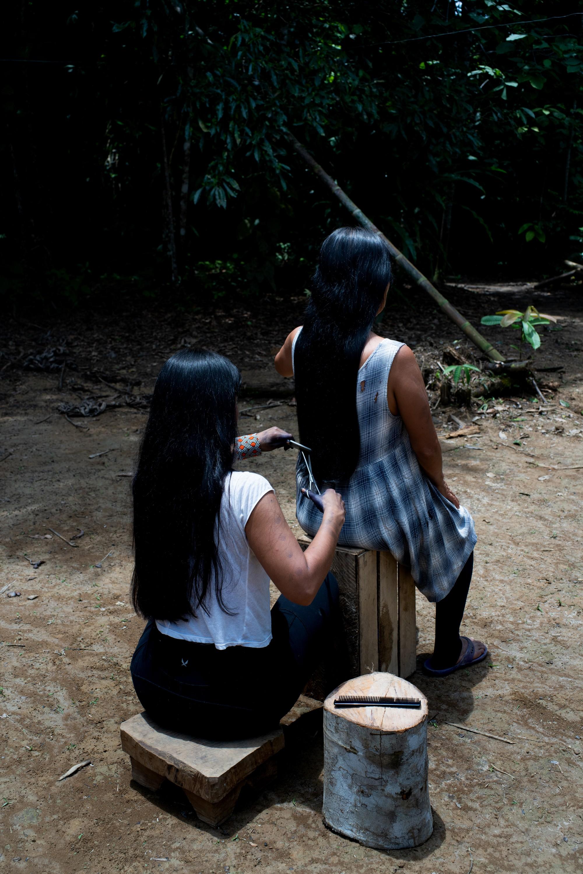 Nina Gualinga corta o cabelo da mãe, Noemi. Ambas as mulheres são membros da Mulheres indígenas coletivas Mujeres Amazonicas, em sua comunidade de Sarayaku no Amazônia equatoriana (Foto: Alice Aedy)