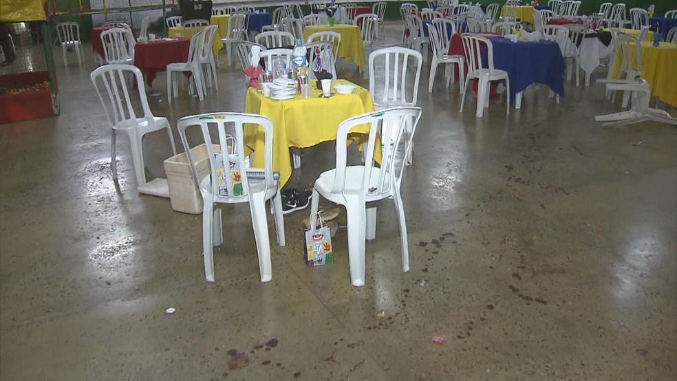 Marcas de sangue em meio a mesas e cadeiras de centro comunitário — Foto: Reprodução/TV Globo