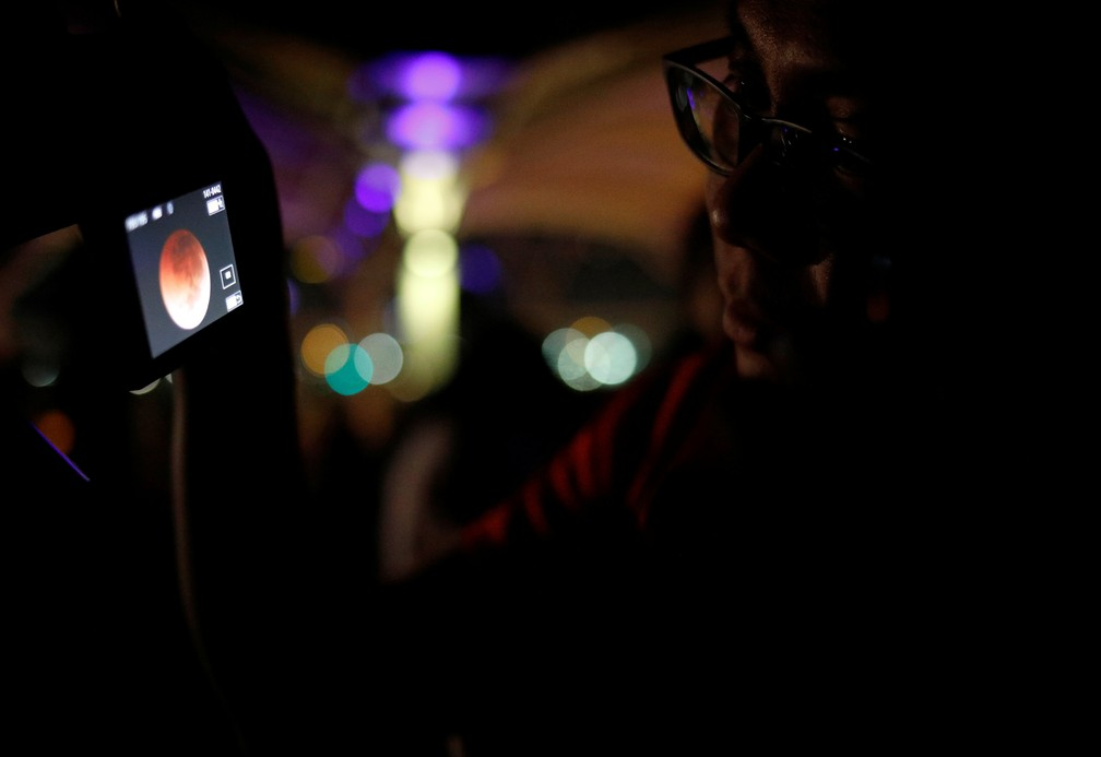 Observador verifica imagem do eclipse lunar registrada em Singapura (Foto: Edgar Su/Reuters)