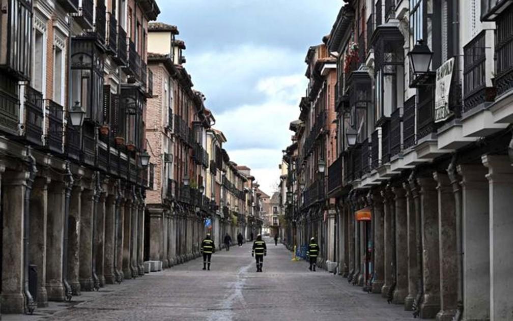 Na cidade de Alcala de Henares, perto de Madri, policiais fazem a ronda em uma rua vazia. Na Espanha, pessoas estão proibidas de sair de casa, exceto para comprar suprimentos essenciais e medicamentos, ou ir ao trabalho  — Foto: Fernando Villar/EPA/BBC
