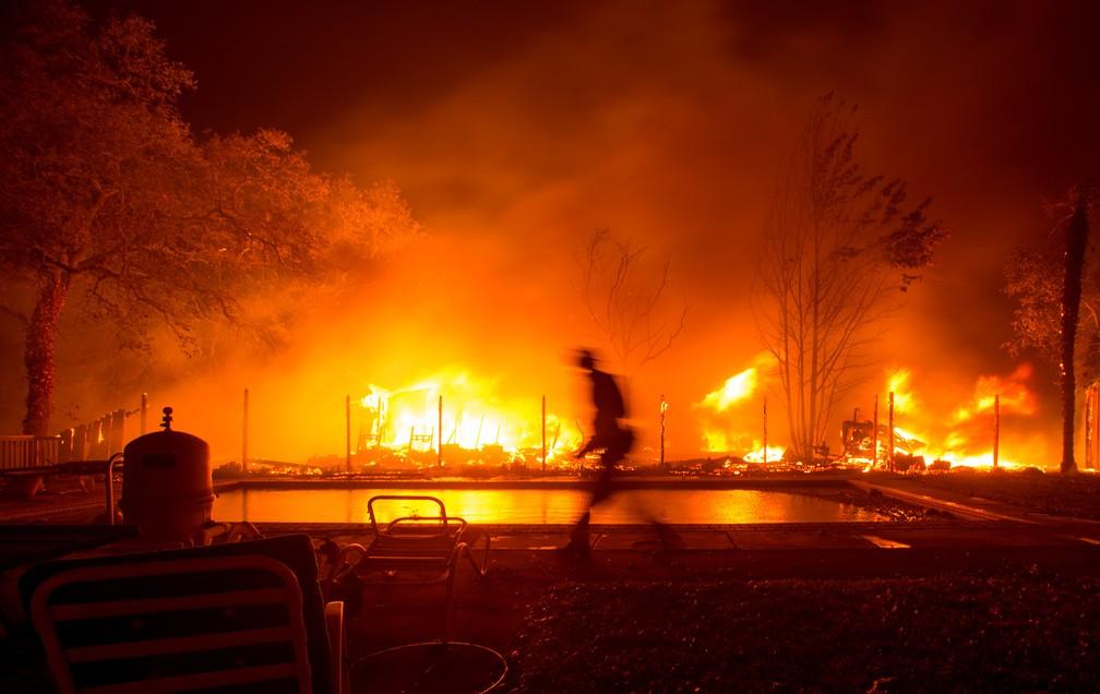 7e6757286 ... 9 de outubro - Um bombeiro caminha perto de uma piscina durante um  incêndio florestal que