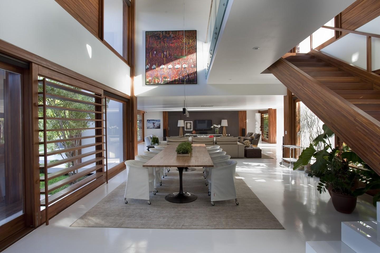 Sala com piso epóxi branco, mesa de jantar de madeira com cadeiras brancas e escada de madeira.