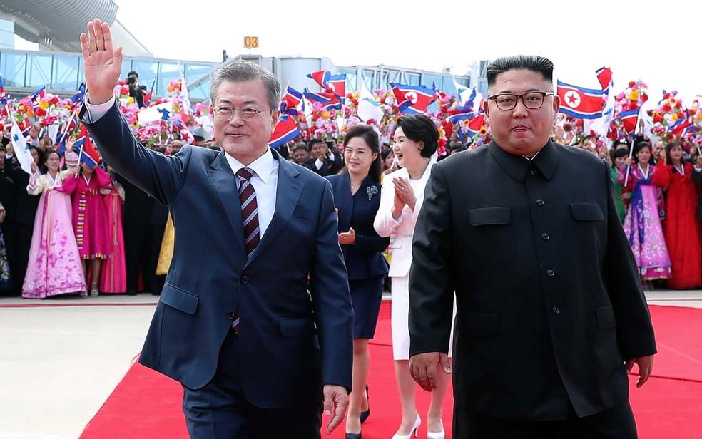 O presidente sul-coreano Moon Jae-in acena ao caminhar ao lado do líder norte-coreano Kim Jong-um no aeroporto de Pyongyang — Foto: AFP