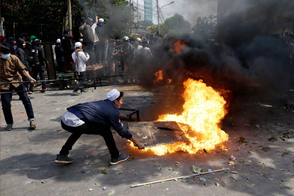 Manifestante tentam apagar fogo durante protesto em Jacarta, na Indonésia, nesta quarta-feira (22)  — Foto: Dita Alangkara/AP