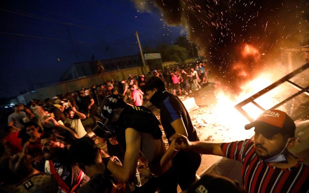 Manifestantes se reúnem em protesto durante toque de recolher, em Bagdá, no Iraque, na noite de quinta-feira (3) — Foto: Reuters/Thaier Al-Sudani