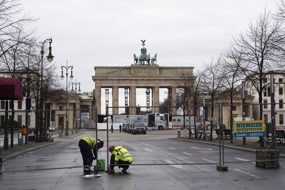 Na Alemanha, policiais cercam a área ao redor do Portão de Brandenburgo, marco de Berlim, na véspera do ano novo — Foto: Associated Press