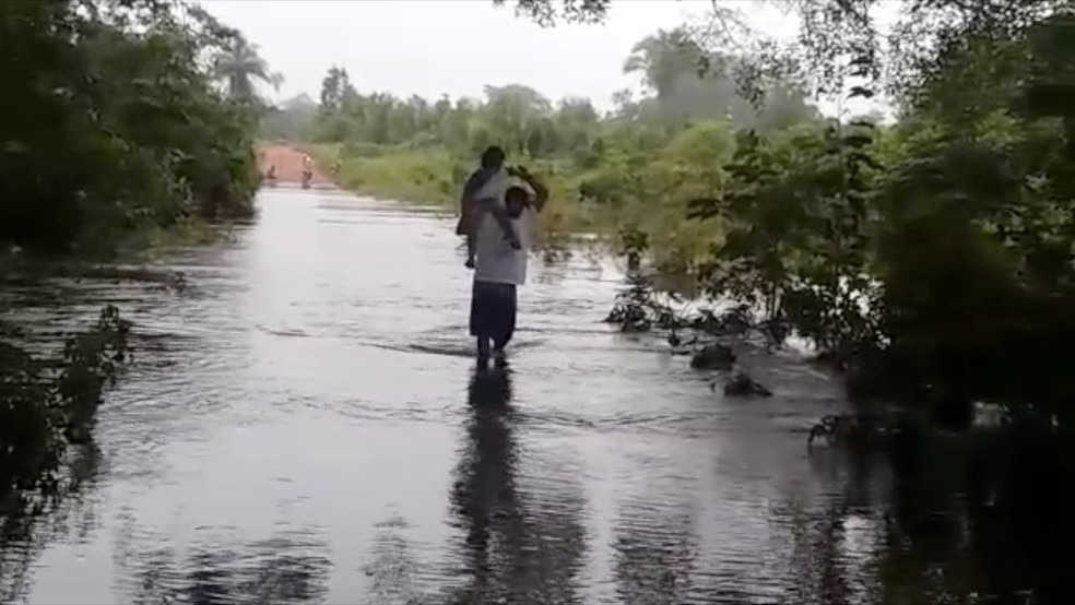 Homem leva criança nas costa dentro de rio (Foto: Reprodução )