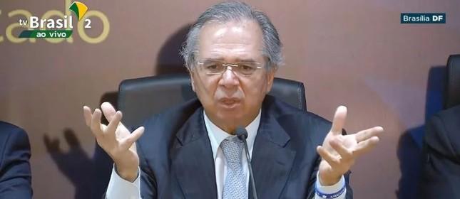O ministro Paulo Guedes em coletiva com a pulseira em referência ao versículo búblico Apocalipse
