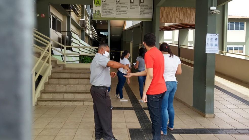 Nos locais de prova, candidatos higienizam as mãos na entrada  — Foto: Aline Nascimento/G1
