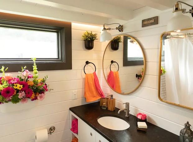 O charme da decoração não é poupado no banheiro, que tem detalhes coloridos e um espelho redondo (Foto: Cindy Ord/ Reprodução)
