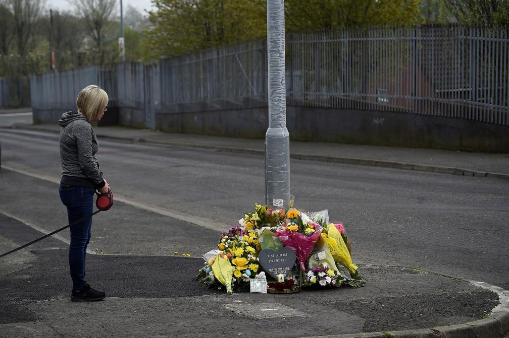 Mulher para e reza junto a flores deixadas no local onde Lyra McKee foi morta a tiros, em Londonderry, Irlanda do Norte. — Foto: Clodagh Kilcoyne/Reuters