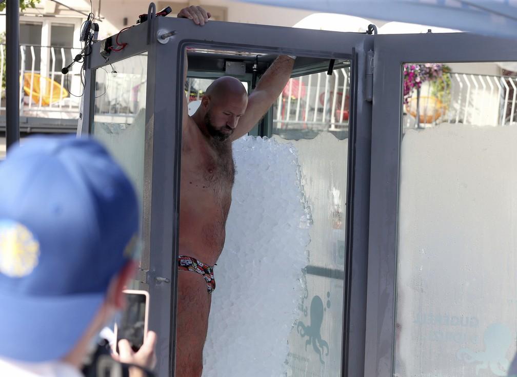 O nadador austríaco Josef Koeberl deixa cabine de vidro cheia de gelo, depois de estabelecer novo recorde dentro de caixa com gelo, em Melk, Áustria — Foto: Ronald Zak/AP