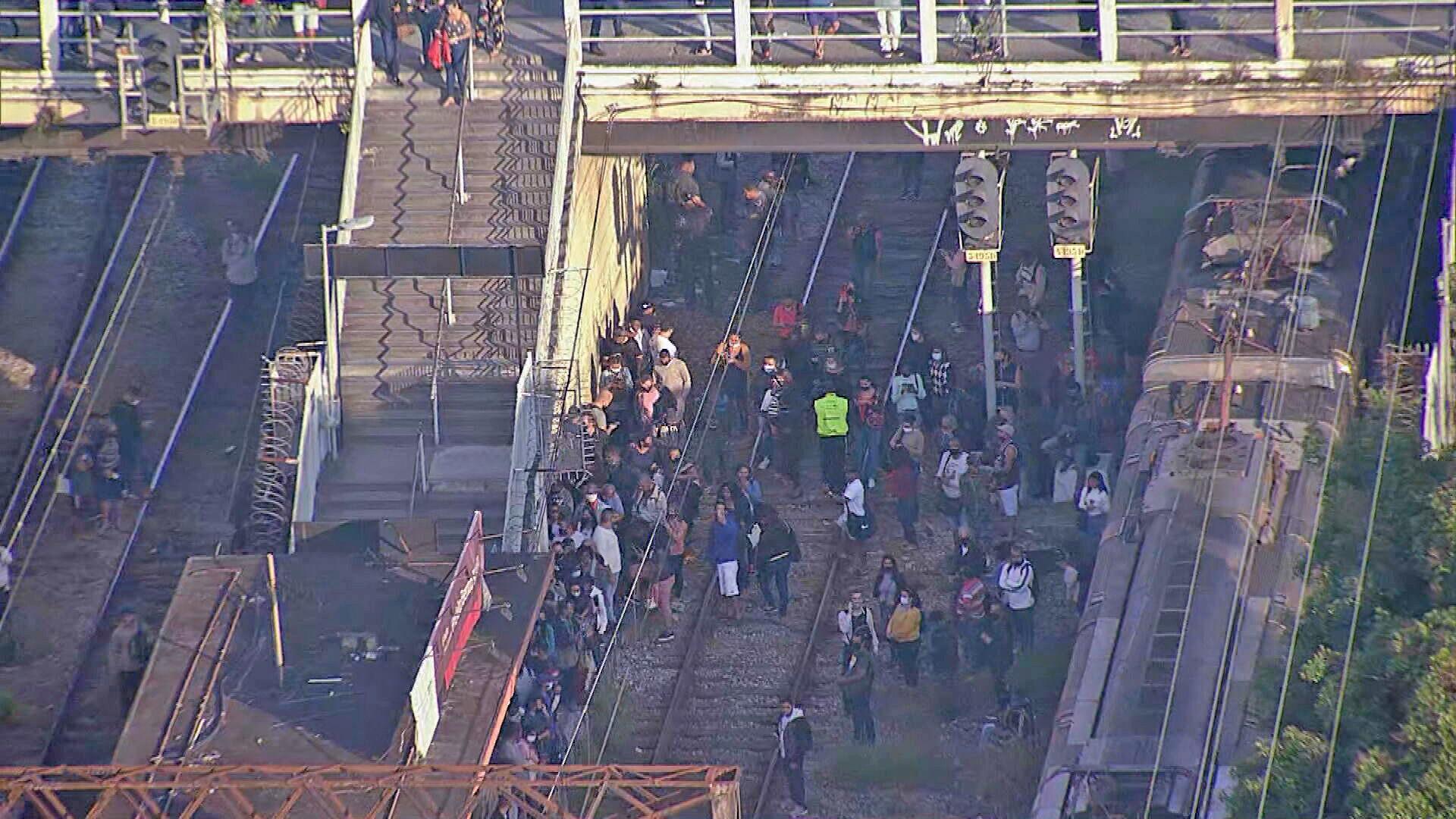 Passageiros desembarcam na linha férrea na estação de Bento Ribeiro e precisam caminhar entre os trilhos