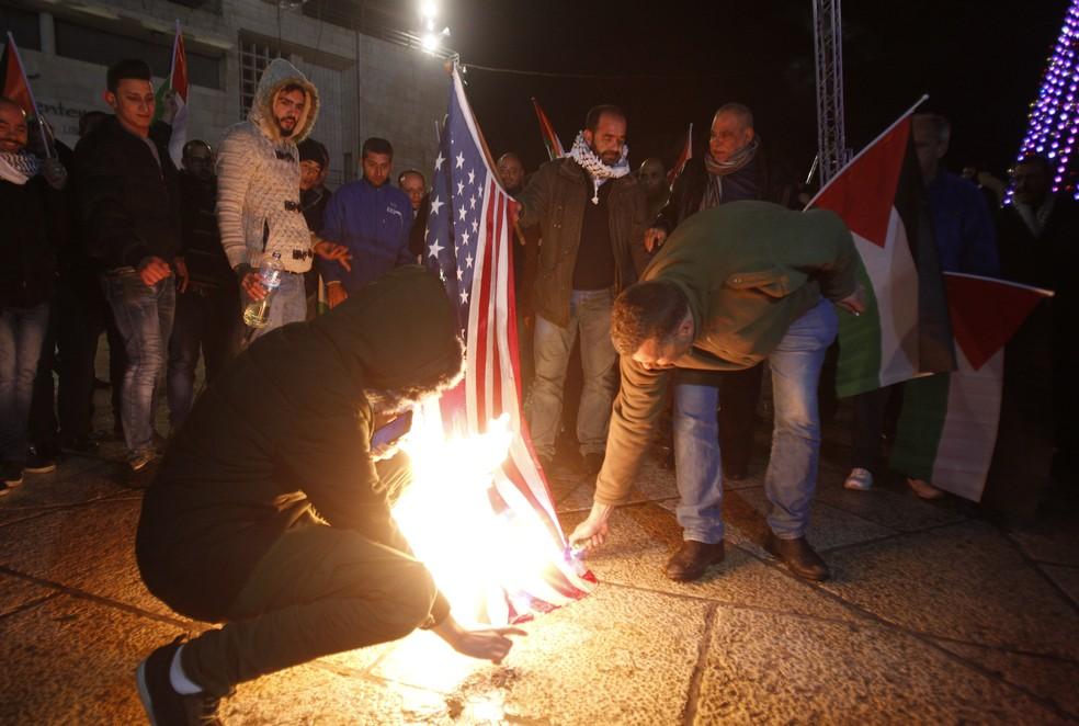 Manifestantes queimam bandeira dos EUA em protesto em Belém após anúncio de Trump de reconhecer Jerusalém como a capital de Israel (Foto: Musa Al Shaer/AFP)