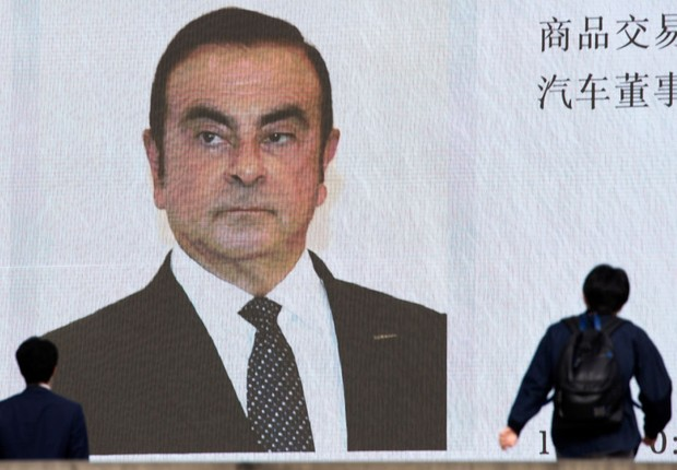 TOKYO, JAPAN - NOVEMBER 20: Pedestrians walk in front of a monitor showing an image of Nissan Motor Co. Chairman Carlos Ghosn in a news program on November 20, 2018 in Tokyo, Japan. Ghosn was detained in Tokyo on Monday over a suspected breach of Japanese (Foto: Tomohiro Ohsumi/Getty Images)