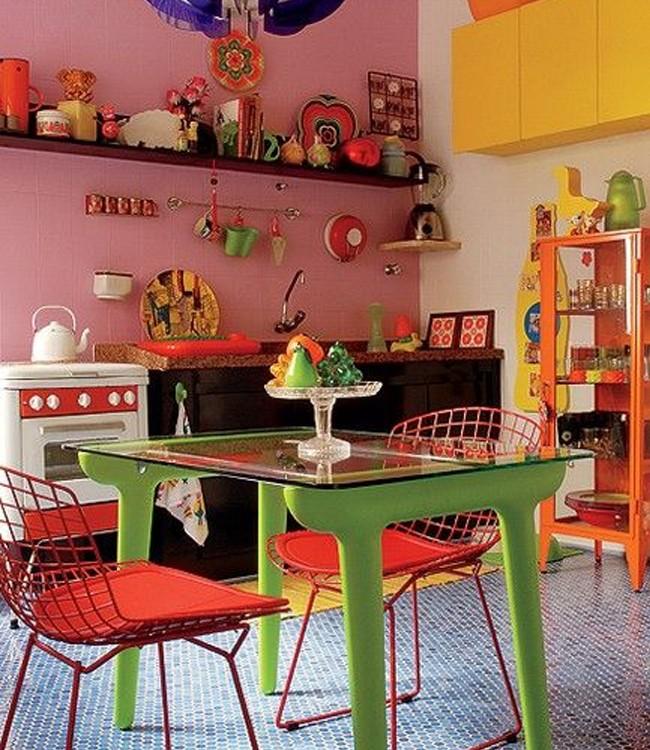 A cozinha original era bege. Mas no projeto do arquiteto Rodrigo Ângulo ganhou piso de pastilhas em vários tons de azul, parede rosa, armários amarelo-flúor e móvel e objetos muito coloridos (Foto: Patricia Cardoso/ Divulgação)