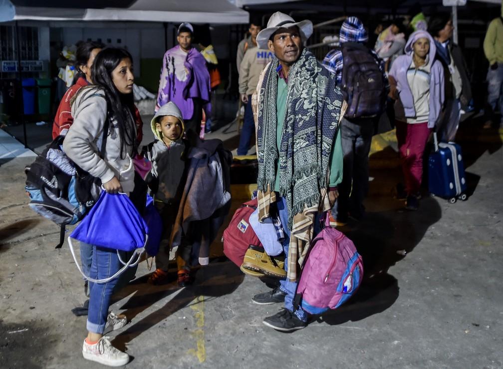 Membros da família Mendoza Landinez esperam para embarcar em ônibus que os levará à fronteira com o Peru (Foto: Luis Robayo/ AFP)