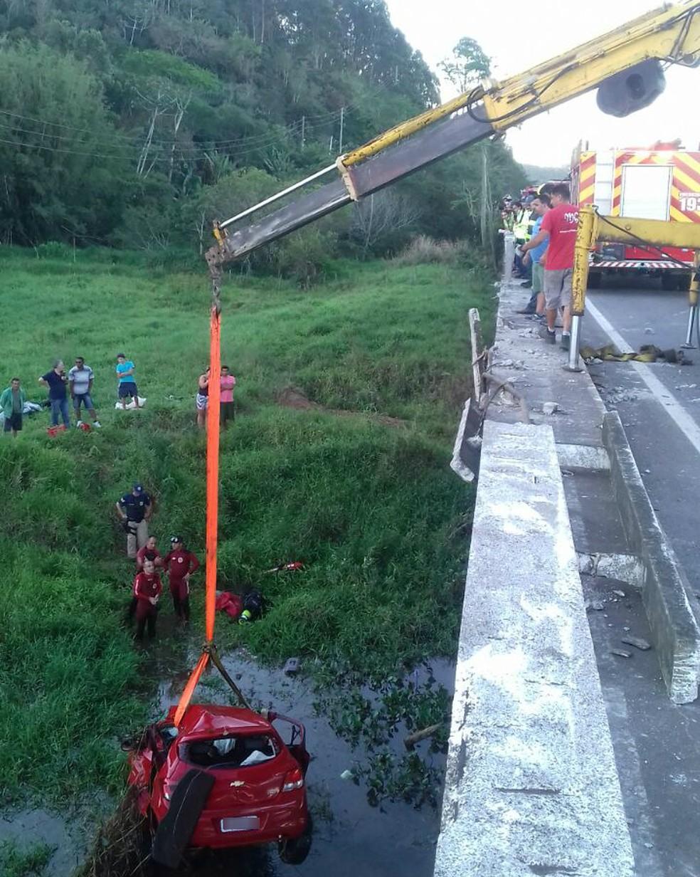 Carro é içado por guindaste após cair no Rio Araçatuba, em Imbituba, na tarde desta quarta-feira (1º). Mulher e duas crianças morreram no acidente. (Foto: PRF/Divulgação)
