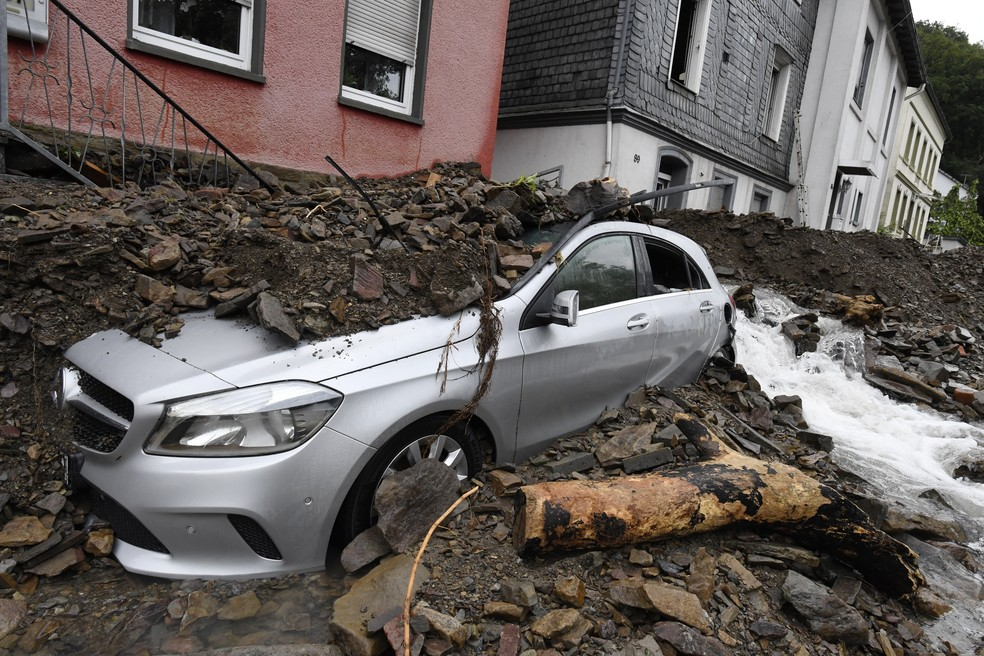 Carro coberto em Hagen, na Alemanha, com destroços arrastados pela enchente do rio Nahma em 15 de julho de 2021. Fortes chuvas transformaram o pequeno rio em uma torrente violenta. — Foto: Roberto Pfeil/DPA via AP