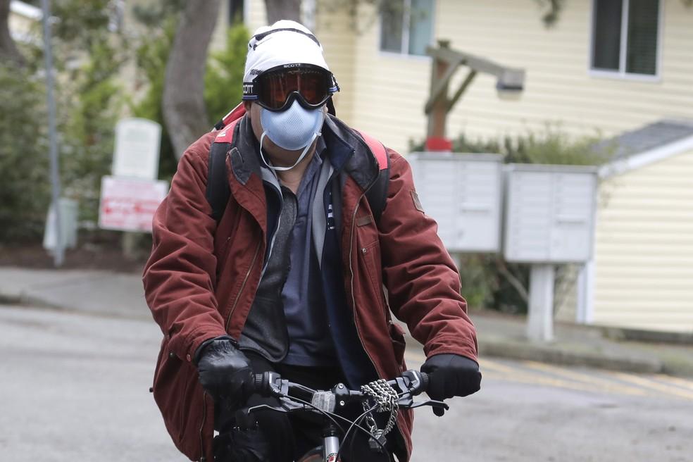 Homem usando máscaras e óculos anda de bicicleta em Kirland, Washington, perto de Seattle, na terça-feira (3). A OMS recomenda o uso de máscaras apenas para profissionais de saúde e pessoas que estão doentes. — Foto: Ted S. Warren/AP
