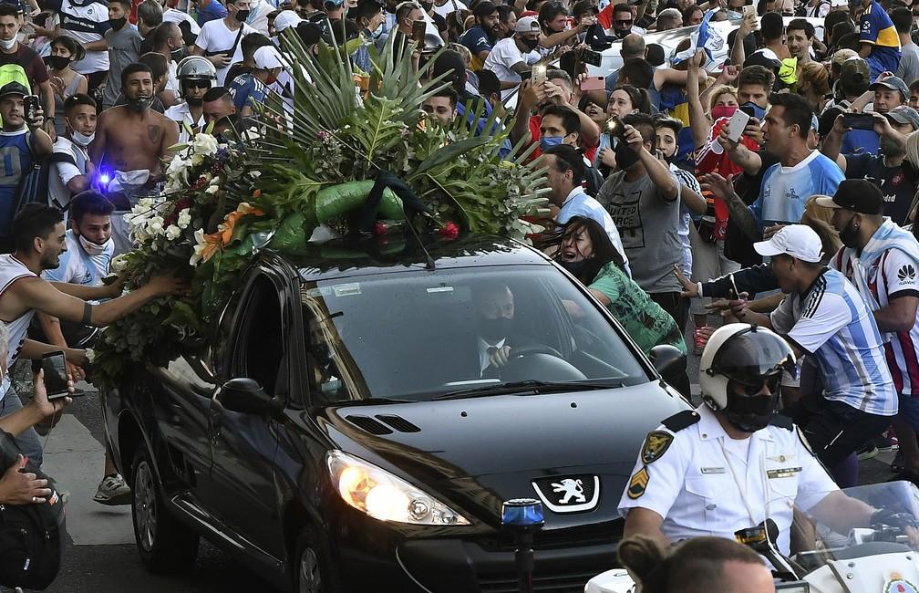 Pessoas se aproximam do carro com corpo de Diego Maradona — Foto: AFP