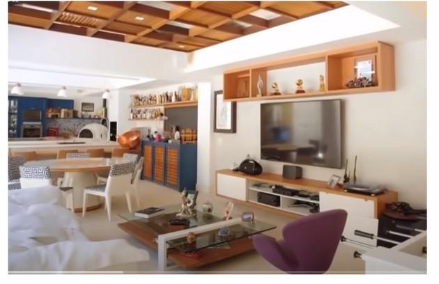 O cômodo é integrado à sala, que tem home theater e decoração em madeira e cores (Foto: Reprodução)