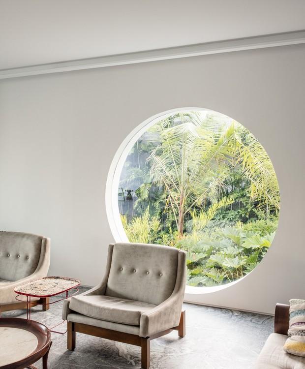 A janela redonda na sala de estar foi inspirada em outros projetos de Niemeyer, trazendo a natureza para dentro de casa (Foto: Stephan Ruiz/ Reprodução)