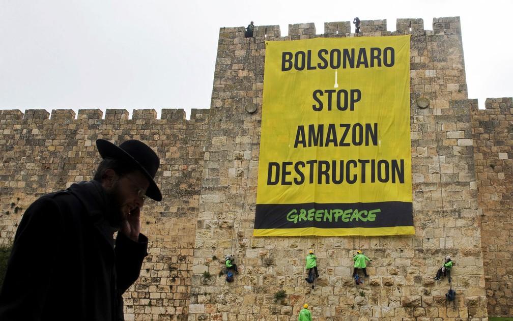 """Ativistas do Greenpeace penduram em muralha da Cidade Velha de Jerusalém banner com a frase, em inglês, """"Bolsonaro, pare a destruição da Amazônia"""", nesta segunda-feira (1º) — Foto: Ohad Zwigenberg/AFP"""
