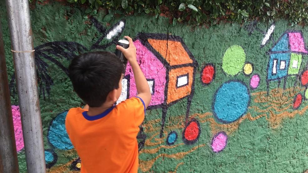 -  Criança participa do mutirão que grafita muros na periferia da Grande Belém: arte, tecnologia e informação  Foto: Ascom