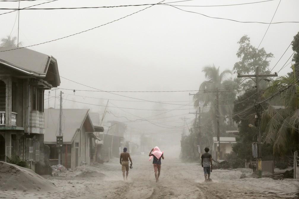 Moradores caminham por rua coberta por cinzas do vulcão Taal em Agoncillon Batangas City, nas Filipinas — Foto: Eloisa Lopez/Reuters