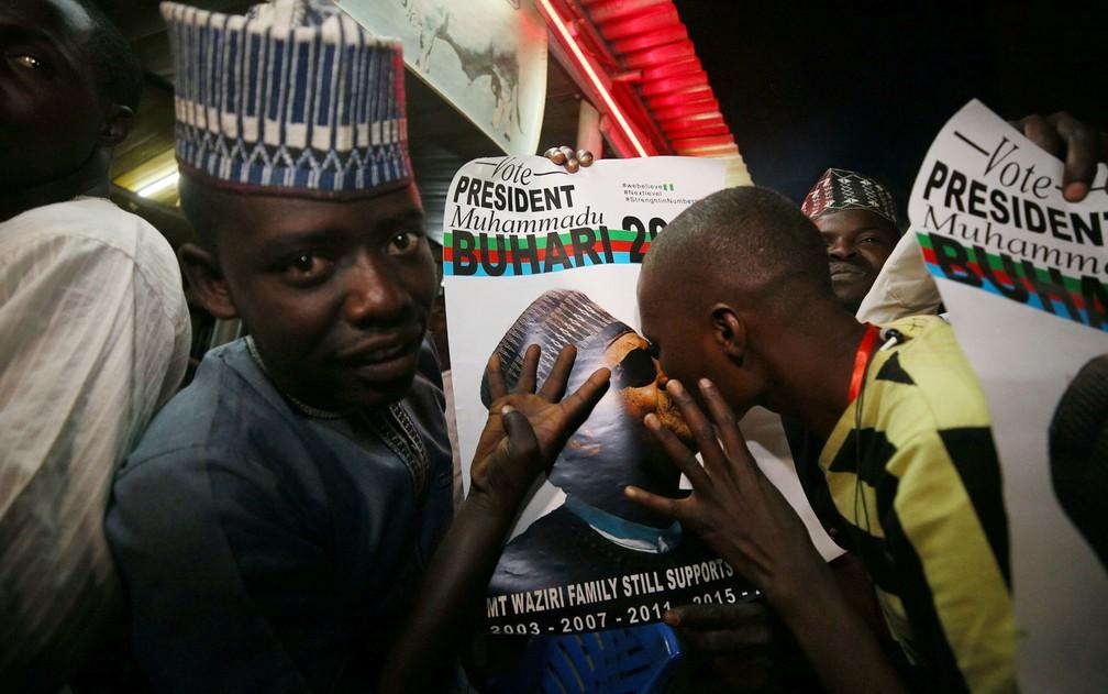Eleitor de Muhammadu Buhari beija uma foto do presidente ao comemorar sua reeleição em Kano, na Nigéria, na terça-feira (26) — Foto: Reuters/Afolabi Sotunde