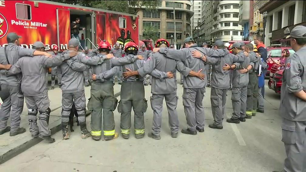Bombeiros fazem oração após término do trabalho de buscas no desabamento do prédio no Largo do Paissandu (Foto: Reprodução TV Globo)
