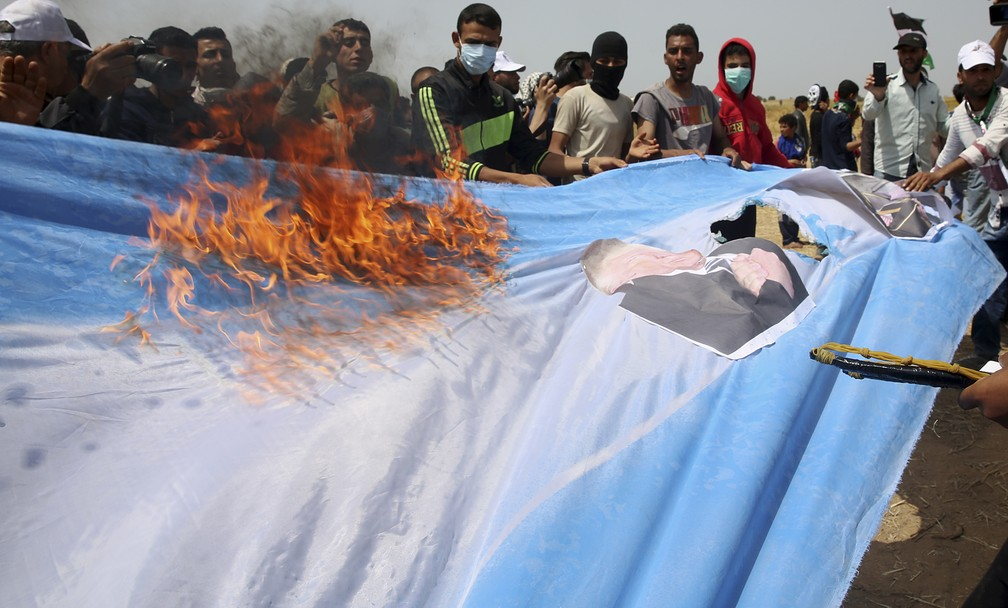 Palestinos queimam bandeira israelense com foto do presidente americano Donald Trump nesta sexta-feira (13) durante protesto em Gaza (Foto: Adel Hana/AP Photo)