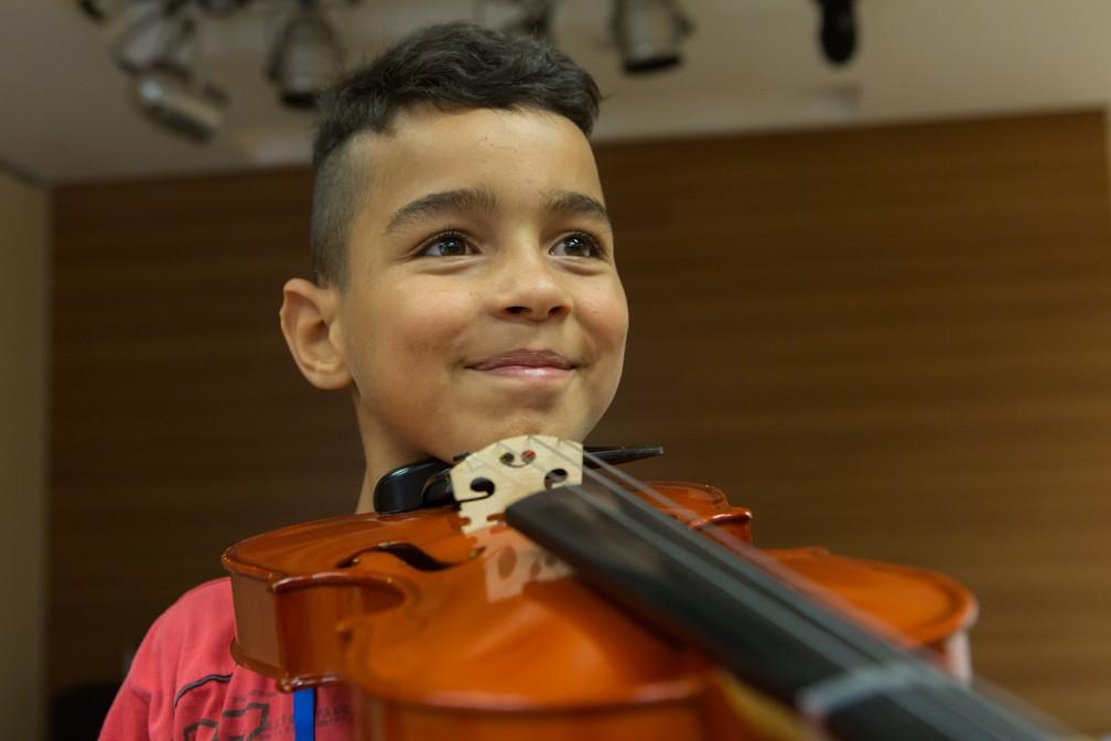 Marcos Alves da Silva, de nove anos, disse que sente amor quando segura o violino (Foto: Celso Tavares/G1)