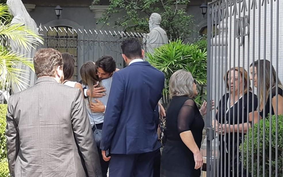 Jorge Sestini, viúvo de Caroline Bittencourt, recebe um abraço na entrada da igreja — Foto: Bárbara Muniz Vieira/G1