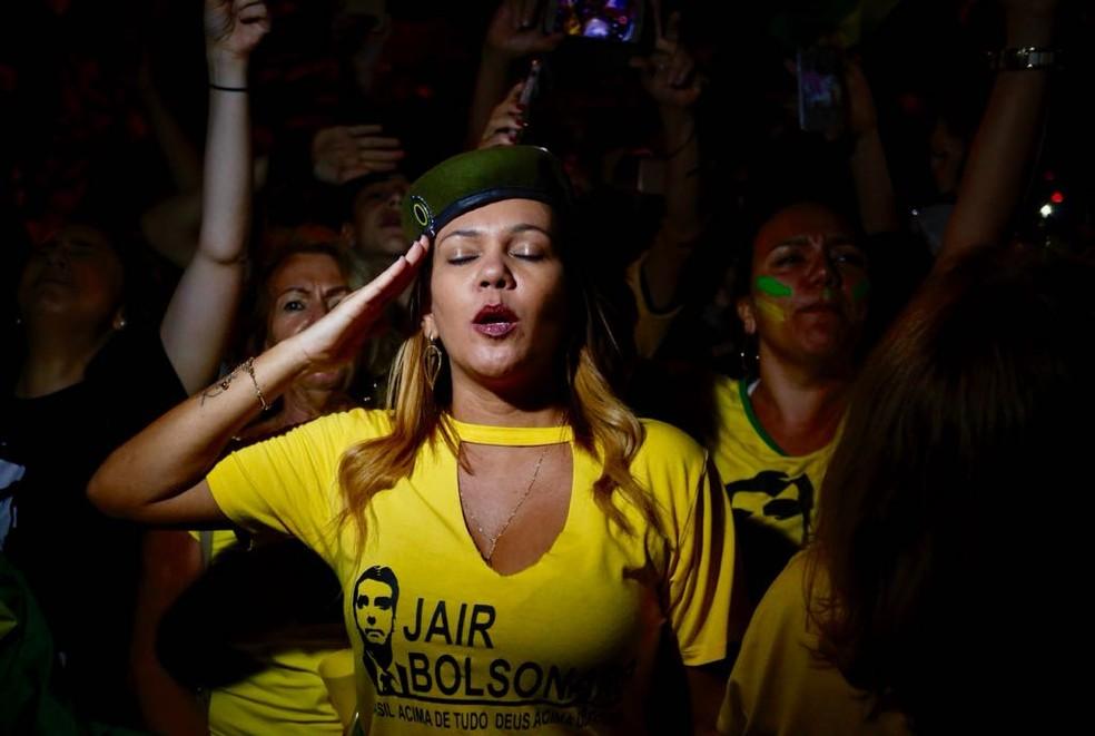 Mulher bate continência durante festa pela eleição de Bolsonaro na Barra de Tijuca, Rio — Foto: Marcos Serra Lima/G1